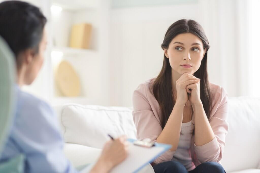 Interested young woman listening carefully to psychotherapist