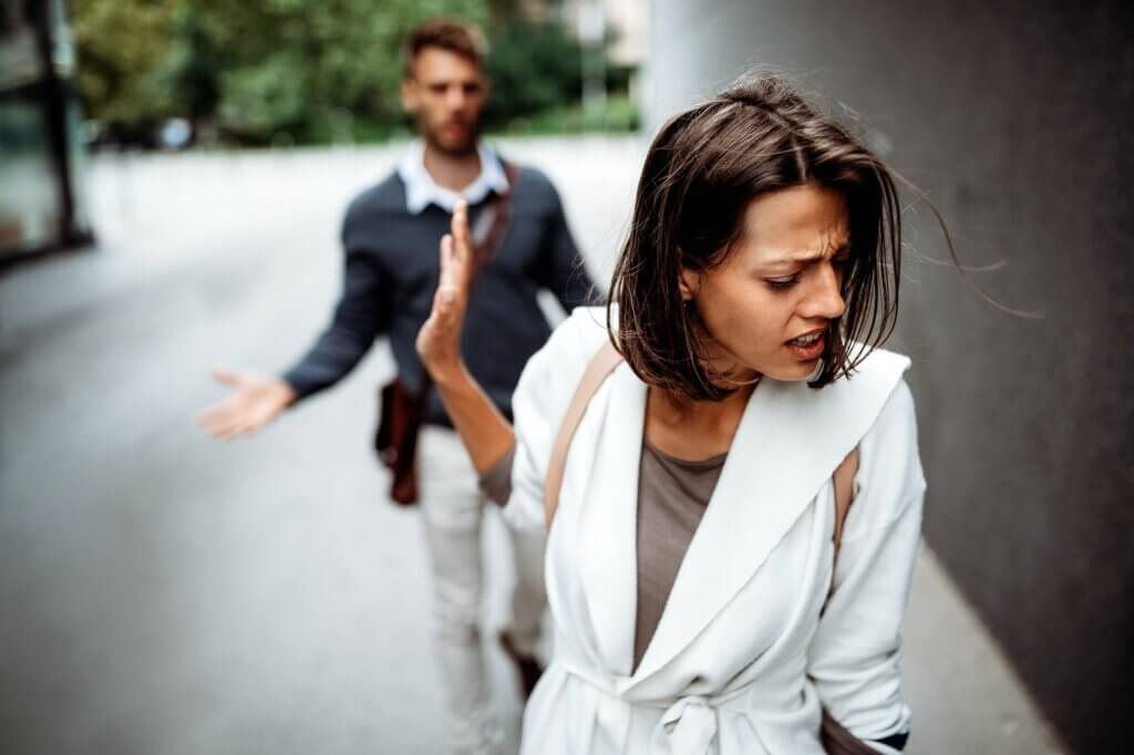 Sad young woman and man outdoor on street having relationship problems