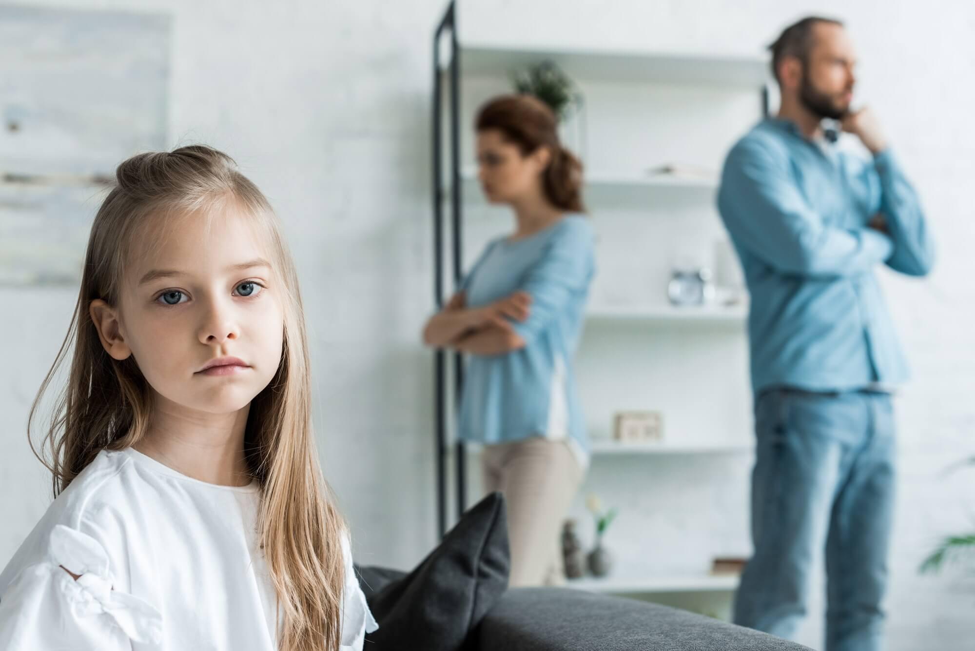 selective focus of sad kid looking at camera near quarreling parents at home